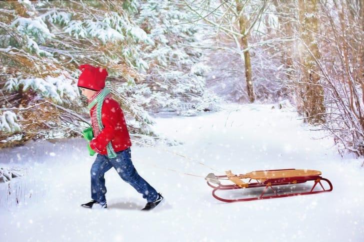 雪の中をそりを引いて歩く子供の写真