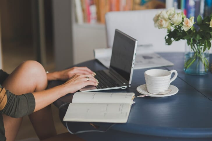 バタフライテーブルでパソコンをする女性の写真