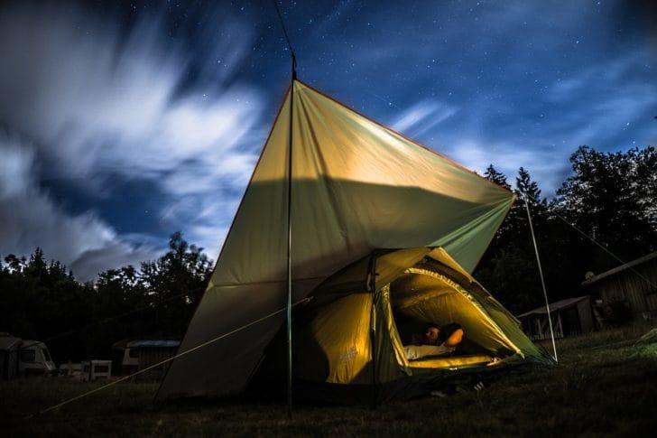 草原にタープを設営してLEDランプを付けている写真