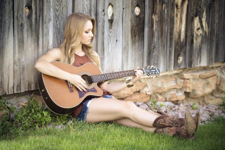 女性が壁にもたれてギターを弾いている写真