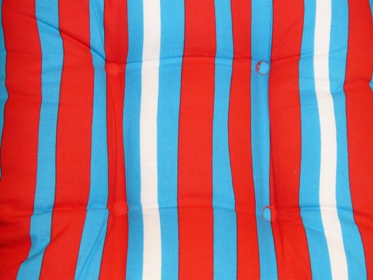 青と赤と白のストライプ柄のクッションカバーの画像