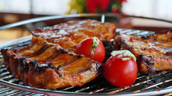 網の上で肉や野菜が焼かれている写真