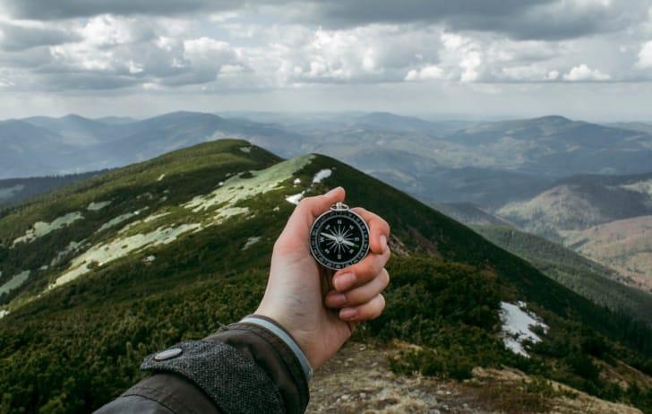 山を背景にコンパスを掲げる手の写真