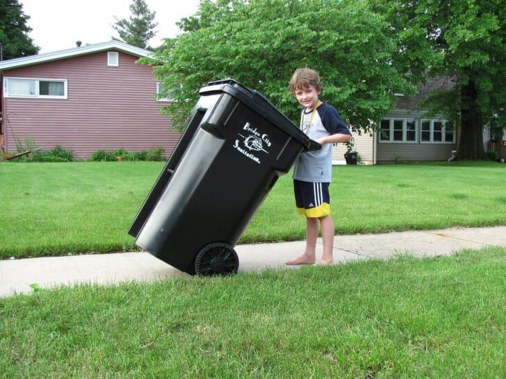 ゴミ箱を持つ少年の写真