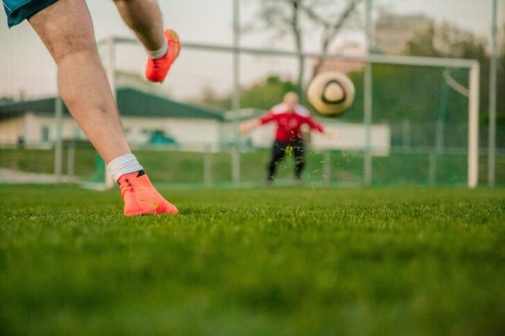 サッカーゴールにシュートしている写真