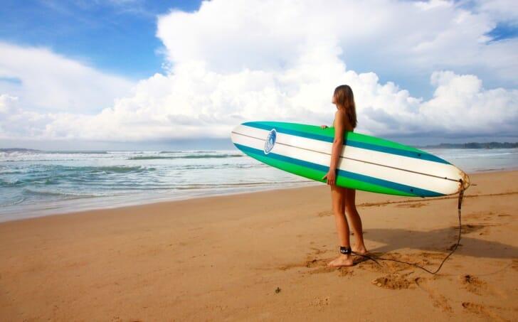 砂浜で女性がサーフボードを抱えている画像