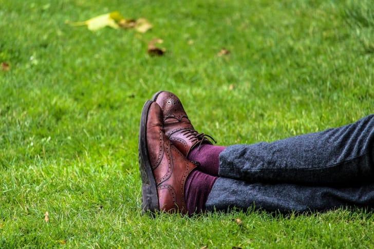革靴を履いた人が芝生でくつろぐ写真