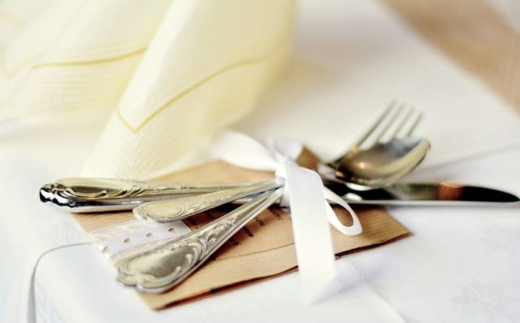 カトラリーがリボンで結ばれてテーブルに置かれている画像