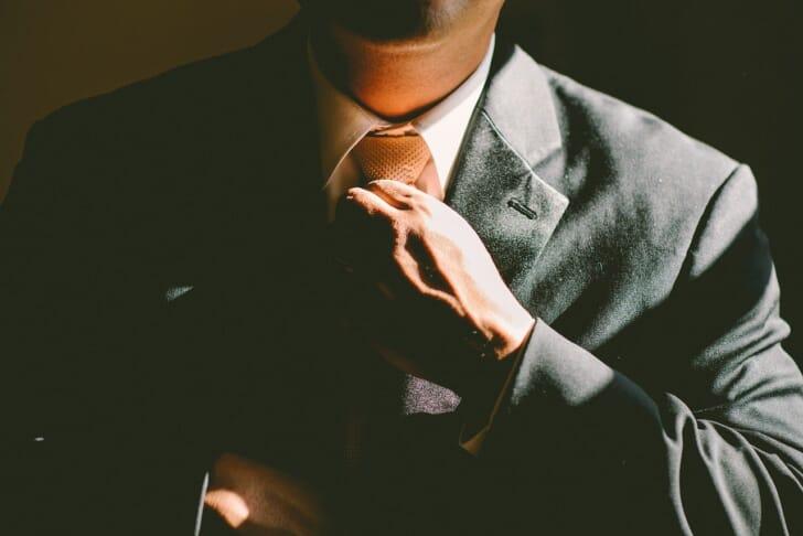 スーツ姿の男性がネクタイを締めている画像
