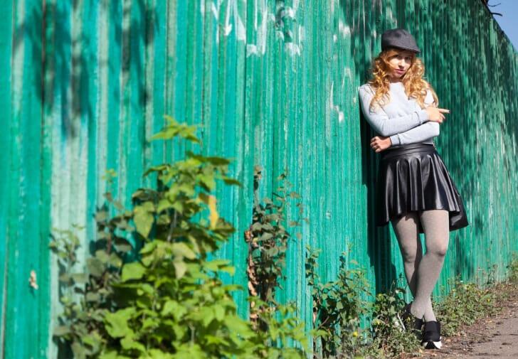 グレータイツにレザーのミニスカートを合わせた女性の写真