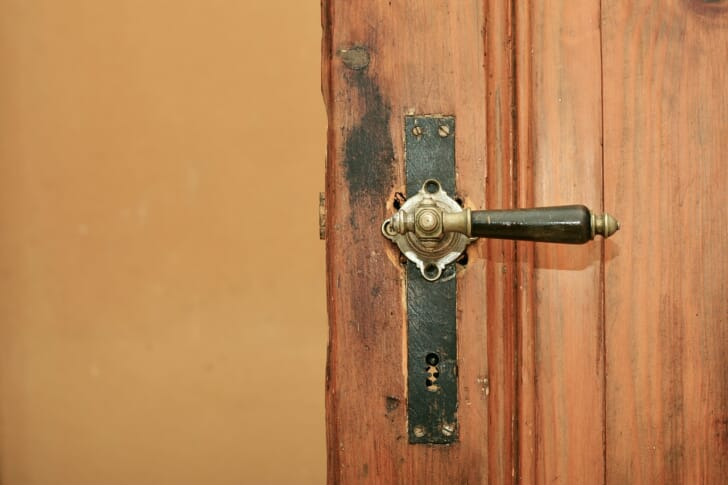 ハンドルタイプのドアノブがついた木製のドアの画像