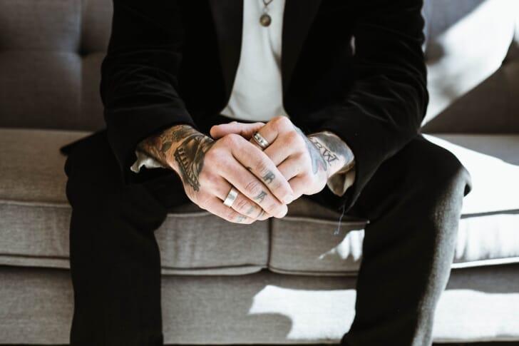 ネックレスや指輪で着飾った黒スーツの男性の写真