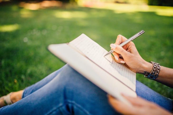 膝の上でノートに書きこみをする写真