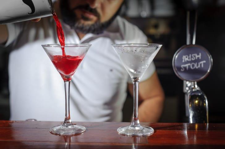 バーテンダーが赤いカクテルをグラスに注いでいる写真