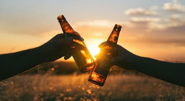 夕日をせにビールグラスで乾杯する写真