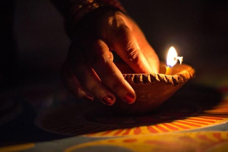 ランプの火をつける手が照らされている画像