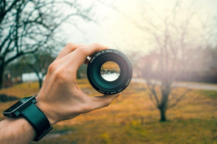 レンズを景色にかざしている写真