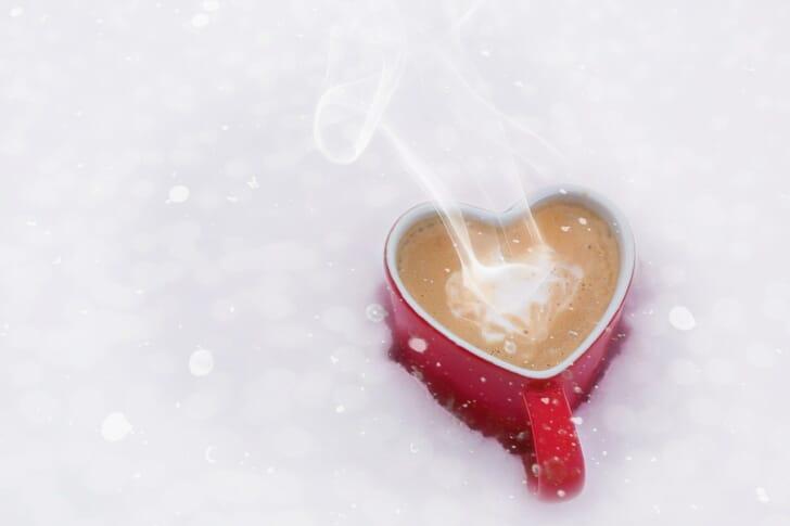 雪の中にカフェラテが置かれている写真