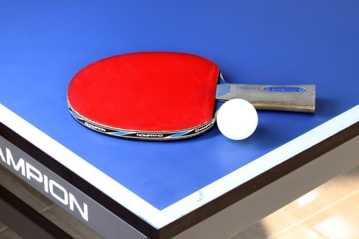 卓球台にラケットと球が置いてある写真