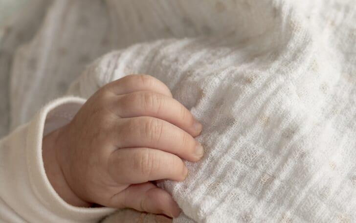 白いガーゼの布を赤ちゃんの手がつかんでいる画像