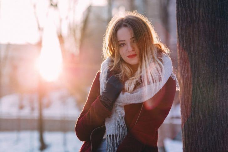 手袋とマフラーをした女性が立っている写真