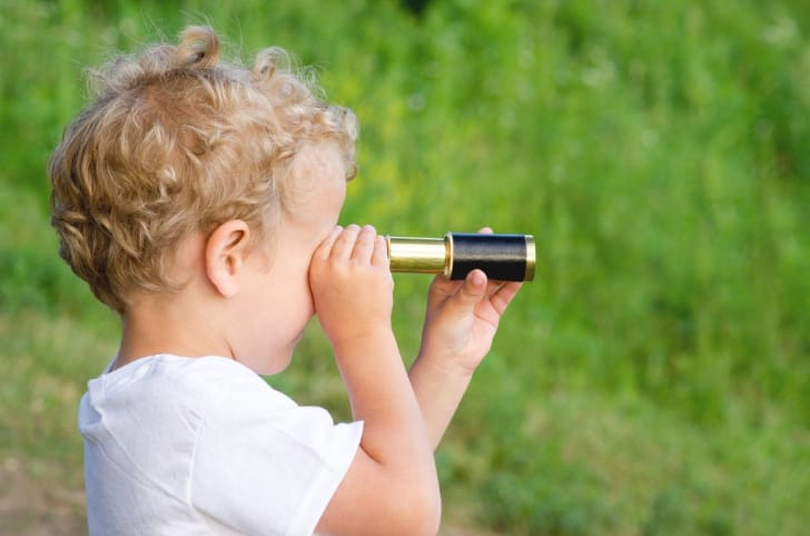 単眼鏡を覗く子供の写真