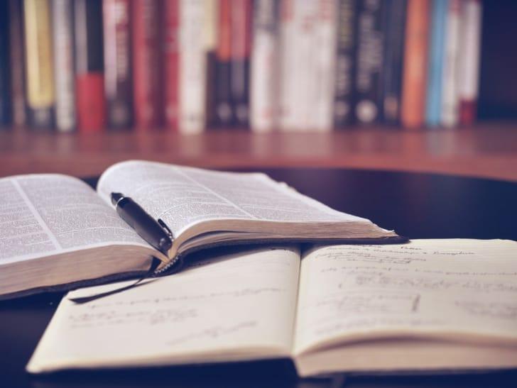 辞書とノートの奥に沢山の本が並んでいる写真