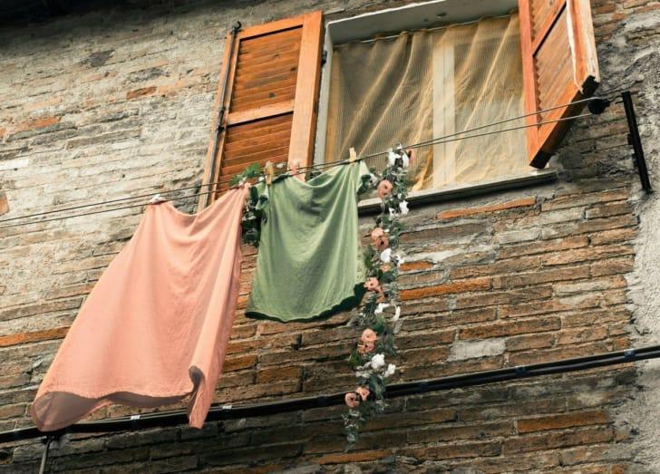 海外のアパートの窓際に洗濯物を干しある写真