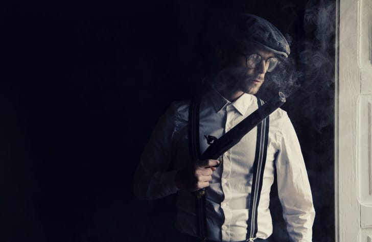 ハンチング帽を被って窓辺にいる男性の写真