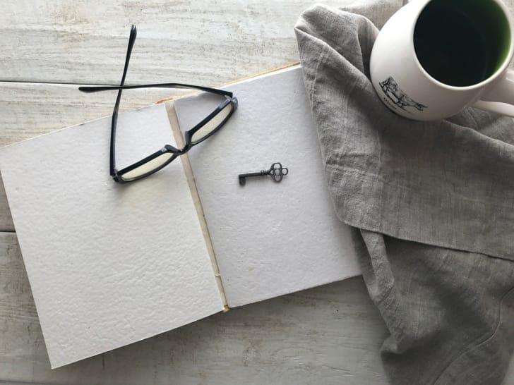 ノートや眼鏡、コーヒーの写真