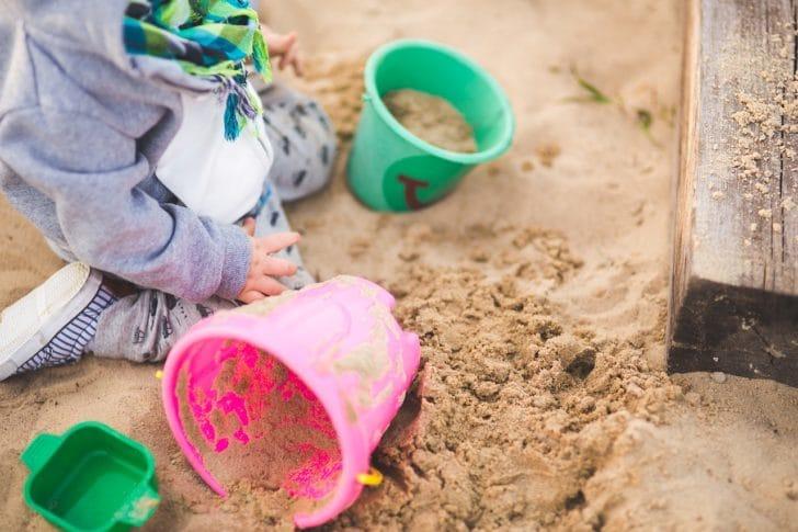 砂場で子供がバケツで遊ぶ写真