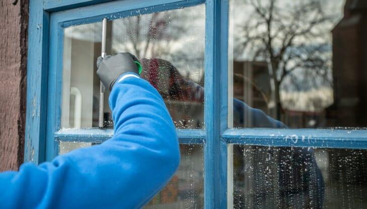 スクイジーで窓を掃除している人の写真