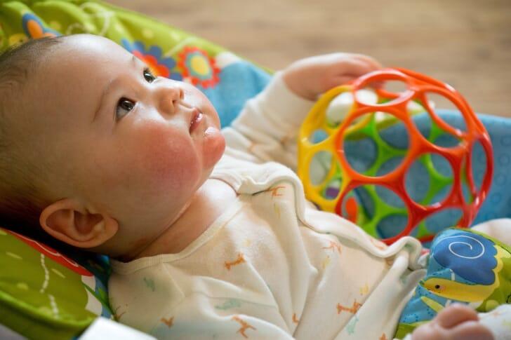 赤ちゃんがおもちゃを持って仰向けに寝ている画像