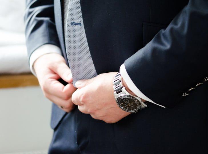 腕時計をつけたスーツの男性の写真