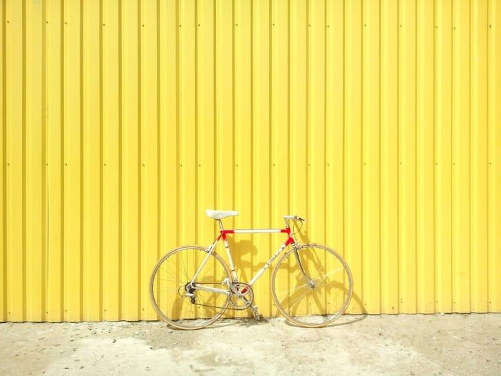 黄色い壁に立てかけられた白い自転車の写真