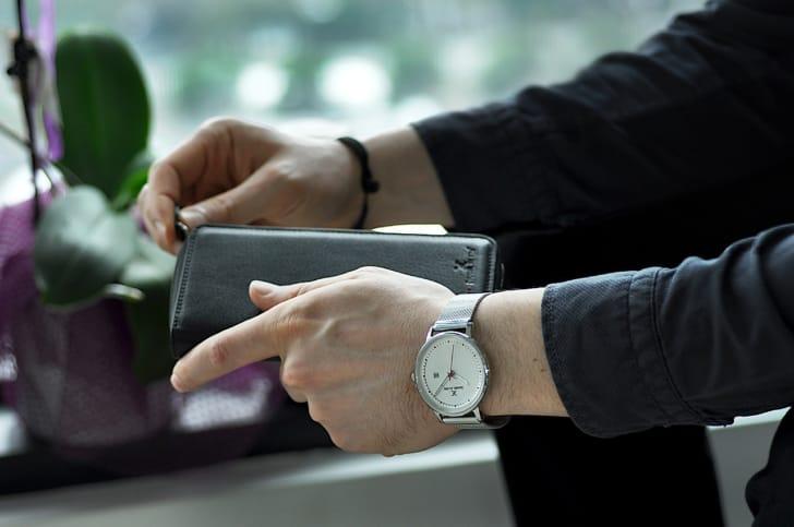 L字ファスナーを開けようとする男性の手元の写真