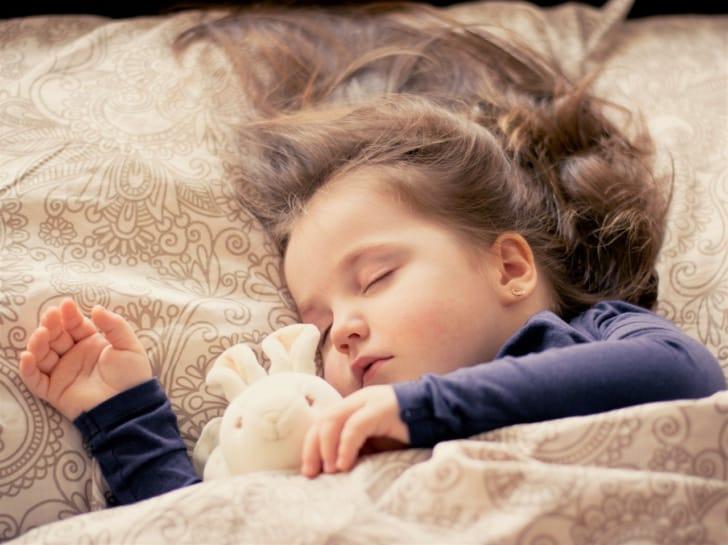 ぬいぐるみと眠る赤ちゃんの写真