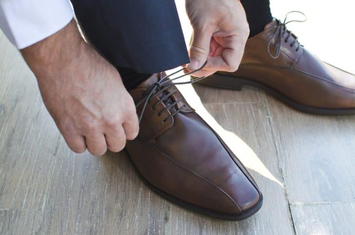 革靴の紐を結ぶ写真