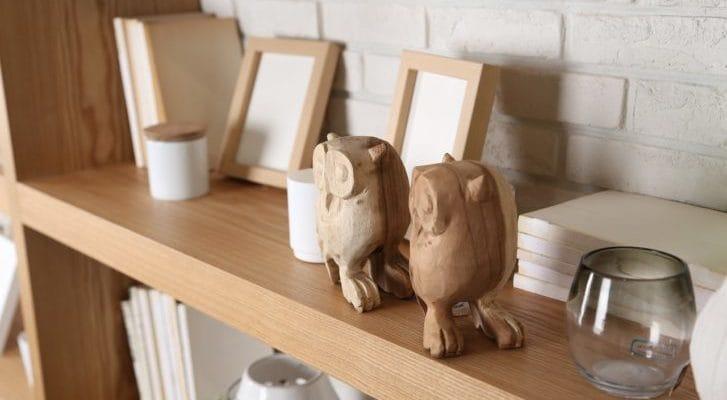 木彫りの梟が置かれた本棚の写真