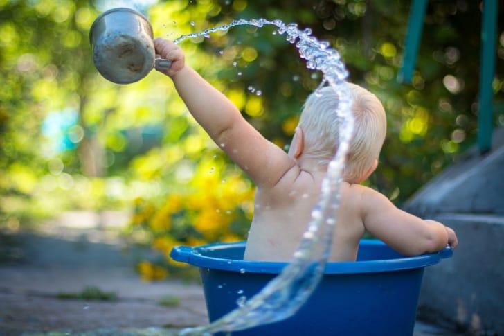 赤ちゃんがタライで水遊びをしている写真