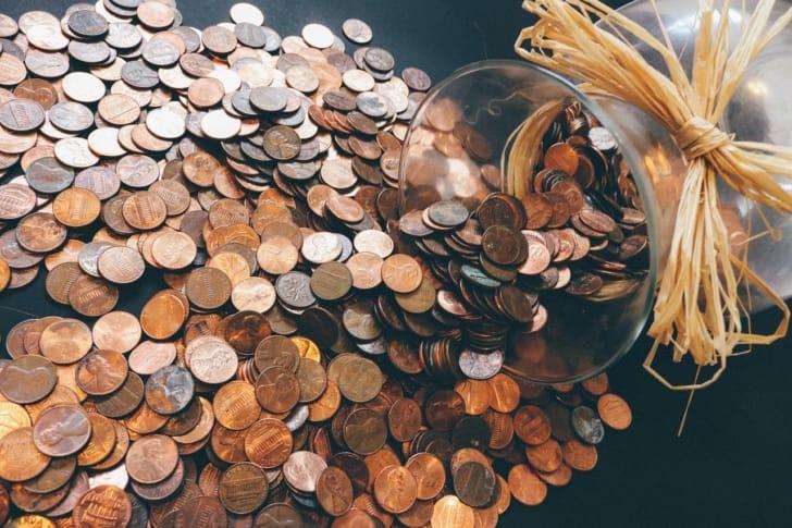 瓶からコインがあふれ出ている写真