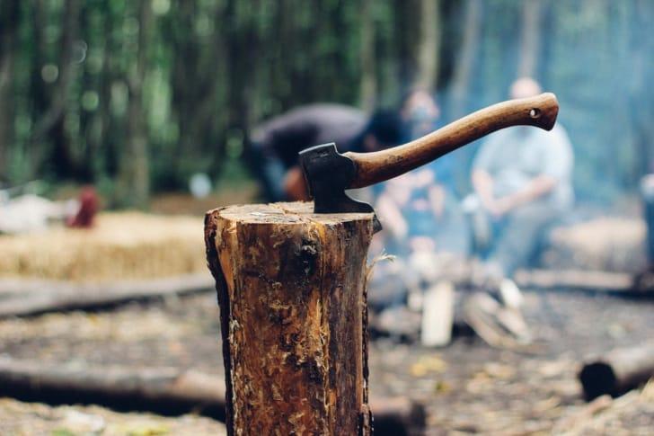 キャンプで手斧で木を割っている写真