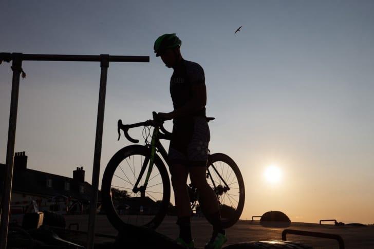 夕暮れ時にロードバイクに乗っている男性の写真