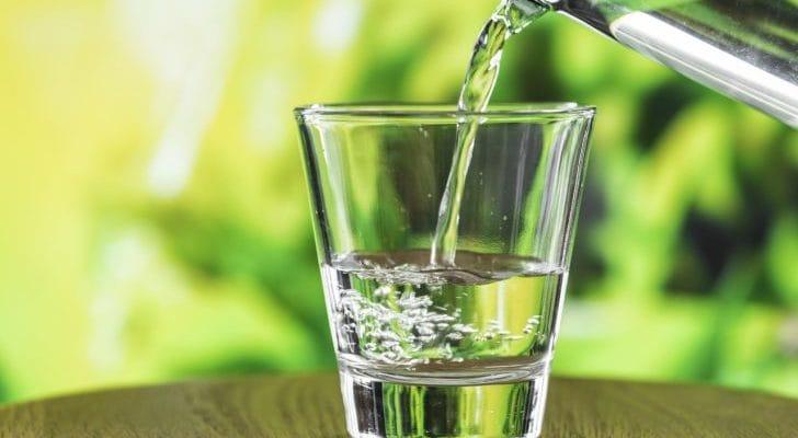 ガラスコップに水を注いでいる画像