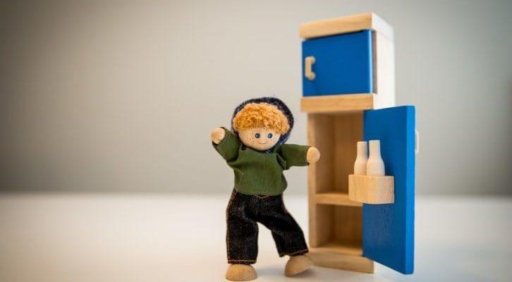 木製の冷蔵庫と人形の男の子の写真