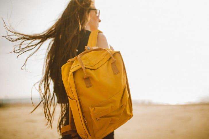 黄色いリュックを背負う女性の写真