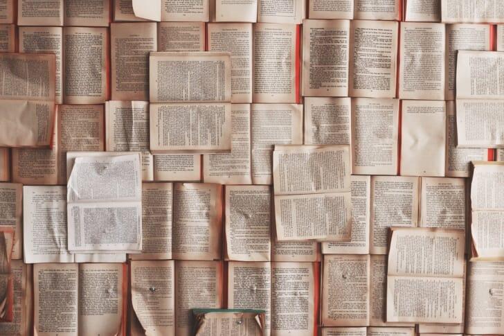 開かれた状態の本がたくさん重ねて置かれている画像