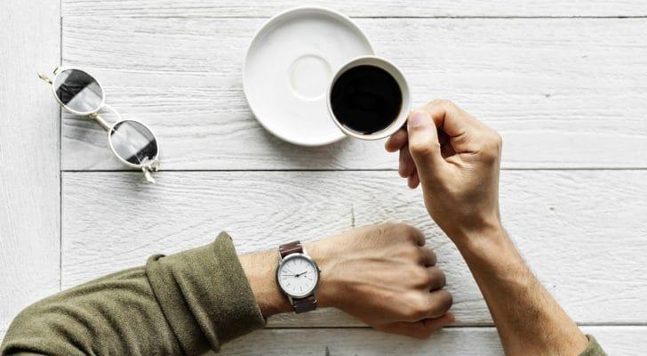 男性がコーヒーを飲みながら腕時計を見ている写真