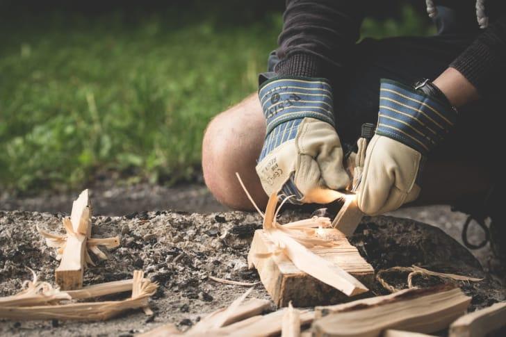 耐熱手袋をはめて火をおこしてる人の写真