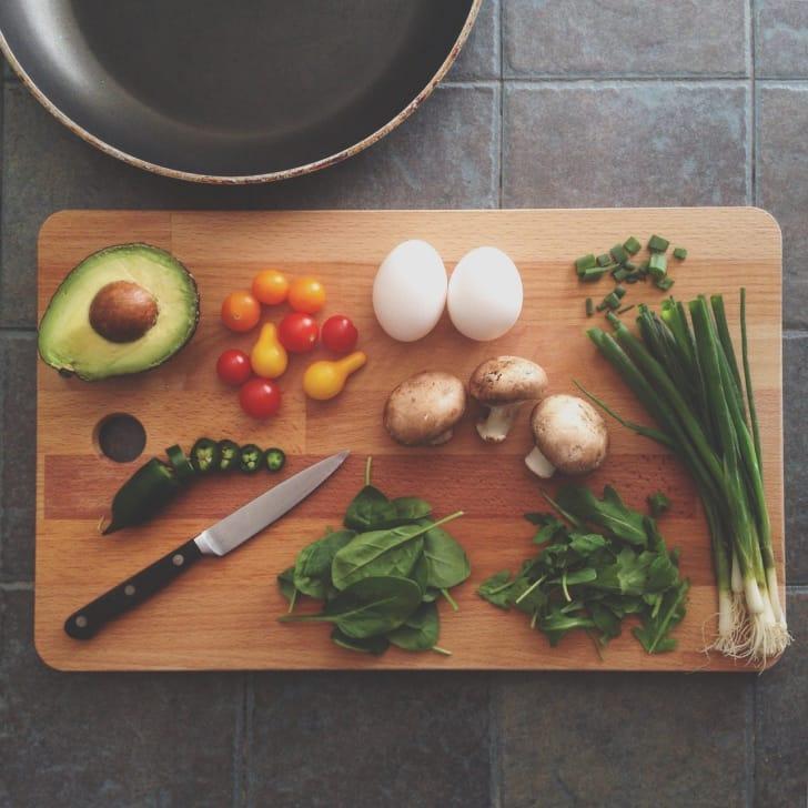 カッティングボードの上に野菜や包丁が並んでいる写真